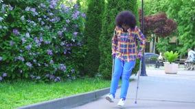 Femme africaine avec une coiffure Afro dans une chemise avec une jambe cassée sur des béquilles descendant la rue MOIS lent clips vidéos