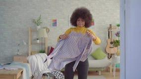 Femme africaine avec une coiffure Afro essayant sur des vêtements devant un miroir en son appartement moderne clips vidéos