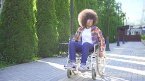 Femme africaine avec une coiffure Afro handicapée dans un fauteuil roulant dans des tours en verre en parc ensoleillé banque de vidéos