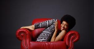 Femme africaine dans la chaise en cuir rouge de bras donnant un coup de pied des jambes par espièglerie Image stock