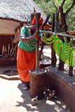 Femme africaine dans la robe multicolore faisant cuire le repas de maïs Images stock