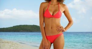 Femme africaine dans les vêtements de bain se tenant sur la plage tropicale Photographie stock libre de droits