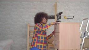 Femme africaine de portrait avec une coiffure Afro à l'aide des outils occupés dans l'ensemble des meubles dans la vie banque de vidéos