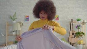 Femme africaine de portrait avec une coiffure Afro essayant sur des vêtements devant un miroir en son appartement moderne clips vidéos