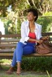 Femme africaine de sourire s'asseyant sur un banc de parc avec un sac Image stock