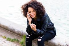 Femme africaine employant avec le téléphone portable à la fontaine de ville Image stock