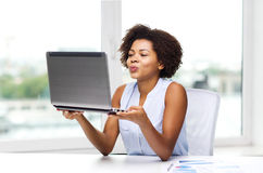 Femme africaine envoyant le baiser à l'ordinateur portable Image libre de droits