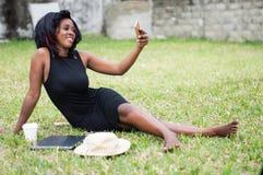Femme africaine faisant un selfie en parc images stock
