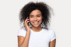 Femme africaine gaie parlant au t?l?phone portable d'isolement sur gris photo stock