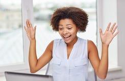 Femme africaine heureuse avec l'ordinateur portable au bureau image stock