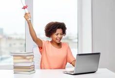 Femme africaine heureuse avec l'ordinateur portable, les livres et le diplôme Photographie stock