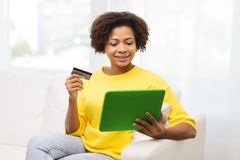 Femme africaine heureuse avec le PC de comprimé et la carte de crédit Photographie stock