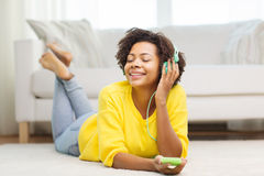 Femme africaine heureuse avec le smartphone et les écouteurs image stock