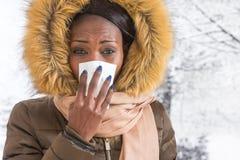 Femme africaine malade de portrait de plan rapproché jeune avec le manteau à capuchon avec la fourrure, fond d'hiver de nez de so photo stock
