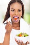Femme africaine mangeant de la salade photos stock