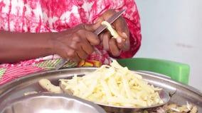 Femme africaine reposant et coupant la pomme de terre dans de petits morceaux clips vidéos