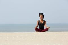 Femme africaine s'asseyant à la plage dans la pose de yoga Image stock