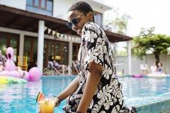 Femme africaine s'asseyant par la piscine appréciant l'heure d'été Image stock