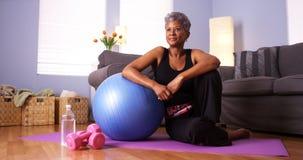 Femme africaine supérieure s'asseyant sur le plancher avec l'équipement d'exercice Photo stock