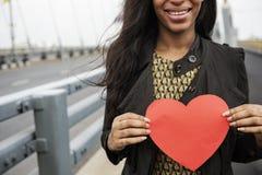 Femme africaine tenant le concept d'amour de symbole de forme de coeur Image libre de droits