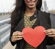 Femme africaine tenant le concept d'amour de symbole de forme de coeur Photographie stock