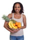 Femme africaine tenant un panier des fruits Image stock