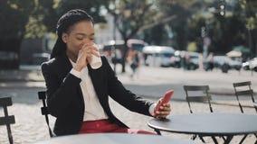 Femme Afro élégante d'affaires utilisant le café potable de smartphone se reposant sur la terrasse d'été en café confortable Mada banque de vidéos