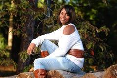 Femme afro-américain s'asseyant sur le logarithme naturel Photos stock