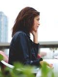 Femme afro-américaine attirante parlant au téléphone intelligent tout en se reposant à la terrasse de café Photo stock