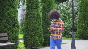 Femme afro-américaine avec une coiffure Afro dans un masque médical protecteur avec un smartphone dans sa main MOIS lent banque de vidéos