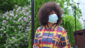 Femme afro-américaine de portrait avec une coiffure Afro dans un masque médical protecteur avec un smartphone dans sa main MOIS l banque de vidéos