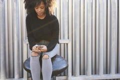 Femme afro-américaine gaie avec du charme participant au programme d'échange dans des loisirs de dépense d'université dehors Photographie stock libre de droits