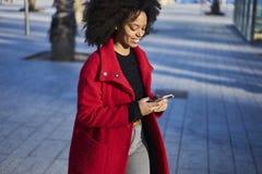Femme afro-américaine gaie avec du charme trouvant la bonne manière avec la connexion sans fil gratuite à l'Internet 4G Image libre de droits