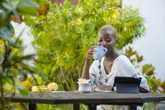 Femme afro-américaine noire attirante heureuse travaillant avec le comprimé dehors au thé potable décontracté ou au café de café  Photographie stock