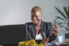 Femme afro-américaine noire réussie d'affaires travaillant au bureau moderne avec des notes d'écriture de téléphone portable sur  photographie stock
