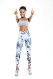Femme afro-américaine sportive montrant des pouces  Images stock