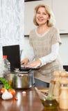 Femme agée à l'aide de l'ordinateur portable tout en faisant cuire la soupe Photos stock