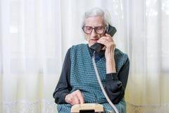 Femme agée à l'aide du téléphone à l'intérieur Photo libre de droits