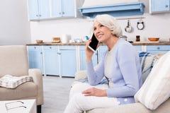 Femme agée à l'aide du téléphone portable à la maison Photos stock