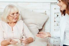 Femme agée agréable prenant des pilules Images stock