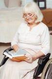 Femme agée agréable s'asseyant dans le fauteuil roulant Photos stock