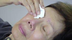 Femme agée appliquant des gouttes pour les yeux sur le lit clips vidéos