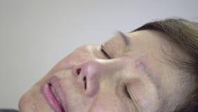 Femme agée appliquant des gouttes pour les yeux sur le lit banque de vidéos