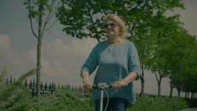 Femme agée appréciant son tour de scooter en nature clips vidéos