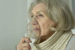 Femme agée avec l'inhalation de grippe Image libre de droits