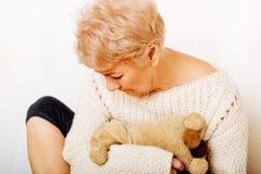 Femme agée avec la dépression se reposant dans le coin Photos stock