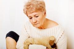 Femme agée avec la dépression se reposant dans le coin Photo stock