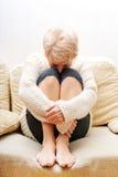 Femme agée avec la dépression se reposant sur le divan Photo libre de droits