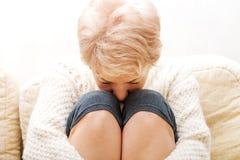 Femme agée avec la dépression se reposant sur le divan Photo stock