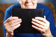 Femme agée avec la tablette images stock